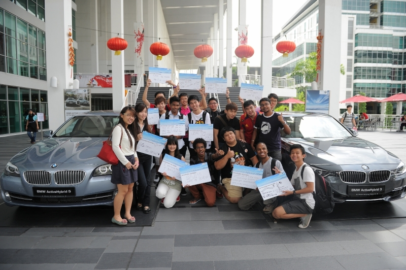 Students of Taylor's Lakeside Campus posing with their written work with the BMW ActiveHybrid 3 Series and BMW ActiveHybrid 5 Series.