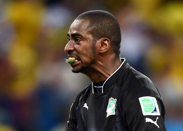 Ivory Coaat goalkeeper Boubacar Barry eating grass